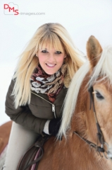 Close-up of a young, pretty woman with a Haflinger horse in the snow in winter